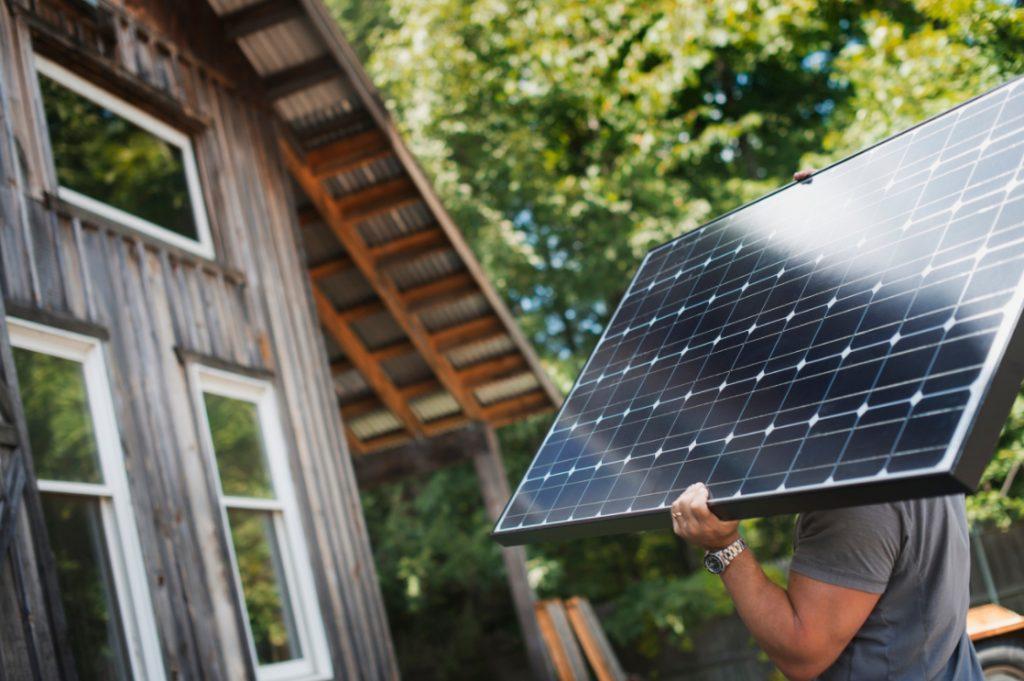 man installing solar panels on a house in brisbane